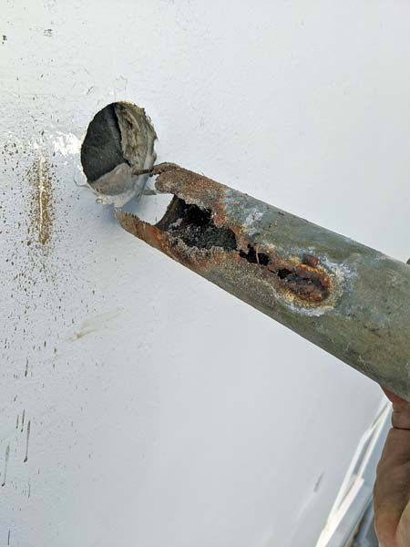 Detached from wall rusted and decayed pipe